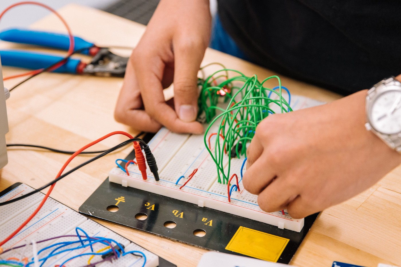 Hands connecting circuits on a circuit board