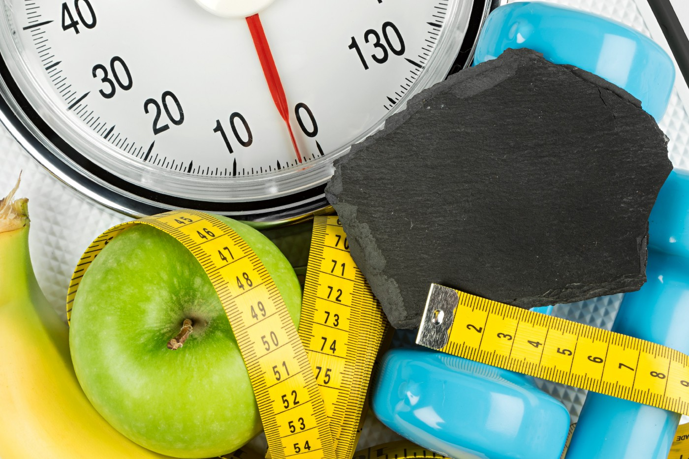 Weights, a tape measure, fruit, and a scale — all things commonly associated with New Year's resolutions