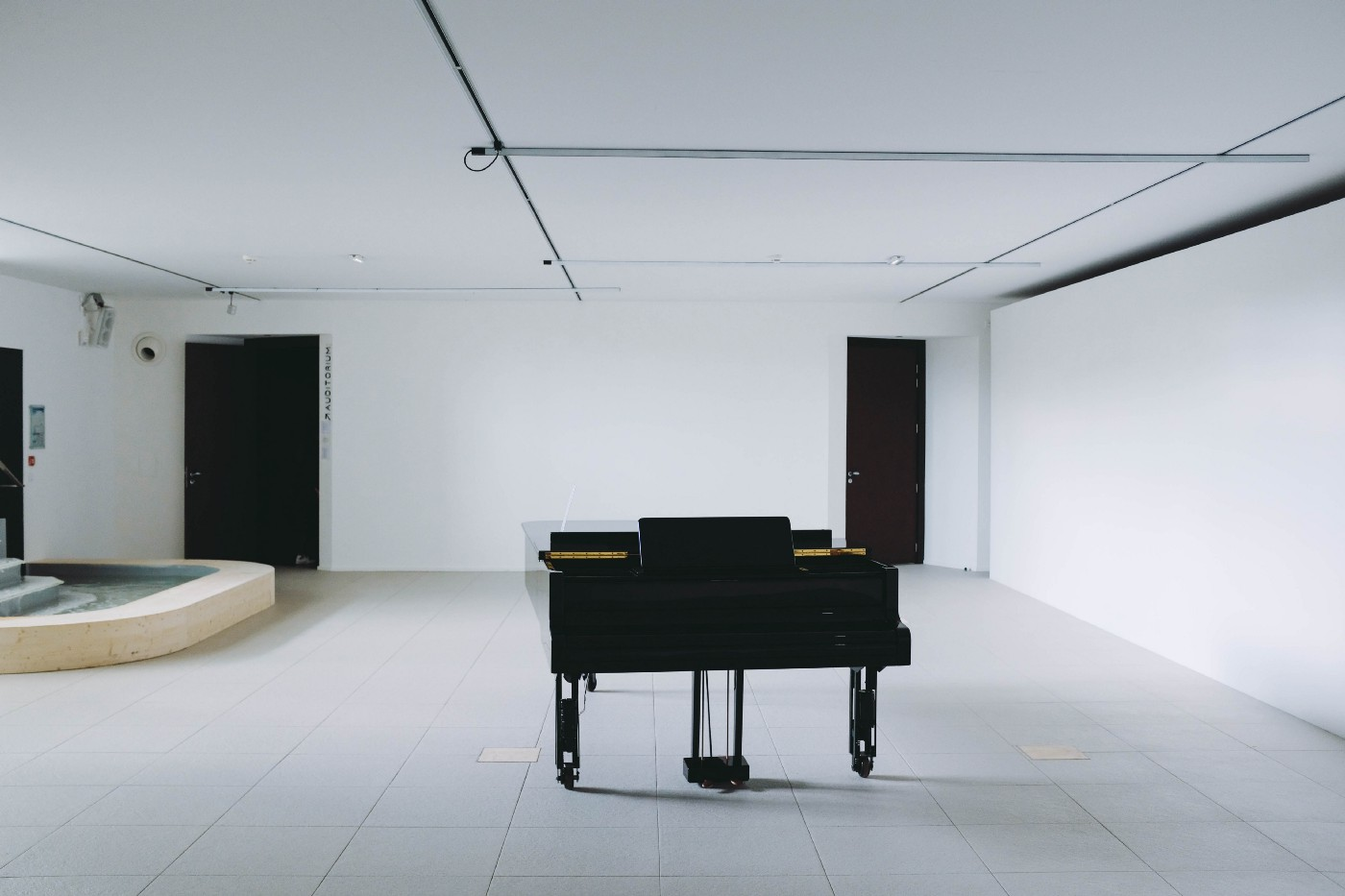 Grand piano in an empty white room