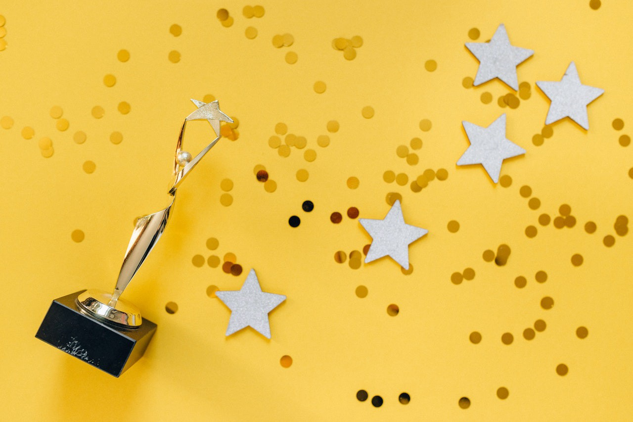 Gold trophy figure holding a star above its head surrounded by confetti and stars on a bright yellow background.