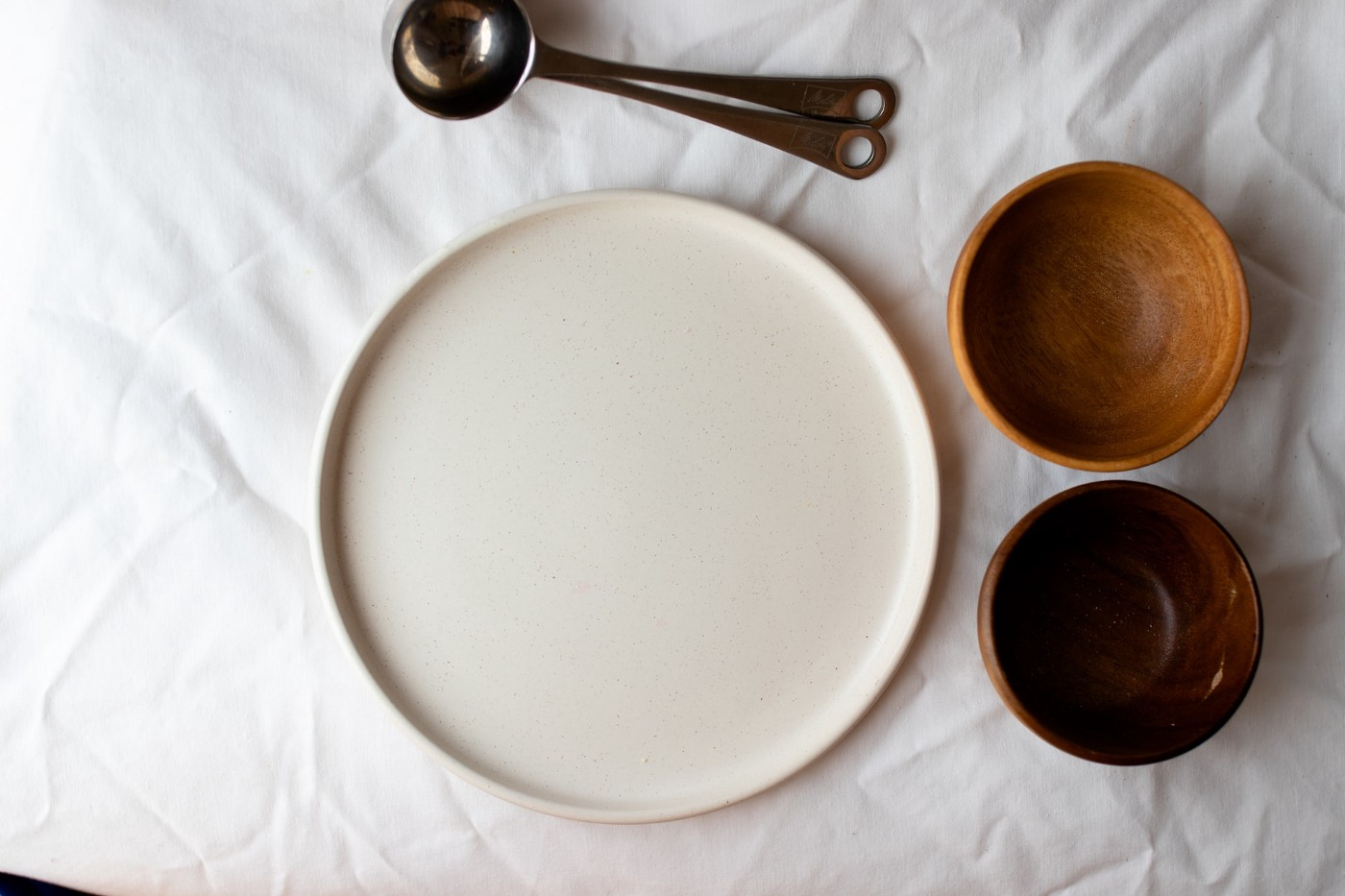 A silver measuring spoon, white plate, one tan bowl and one brown wooden bowl on a white table cloth