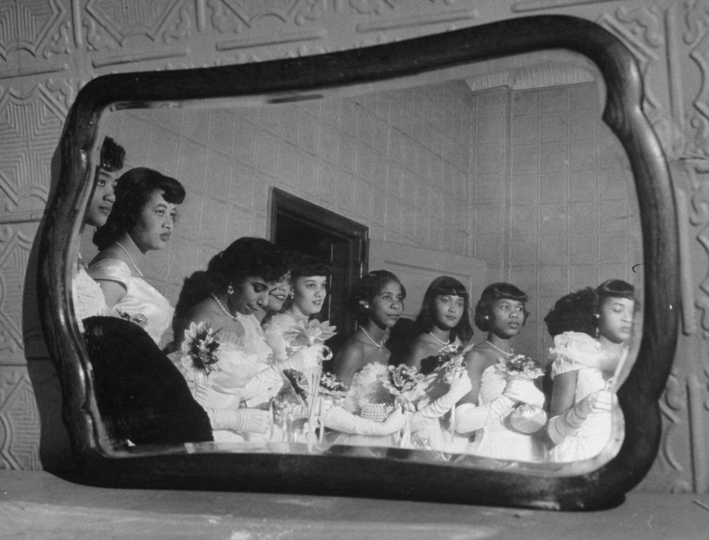 An archival photo of young African American women waiting to go downstairs for their debutante cotillion.