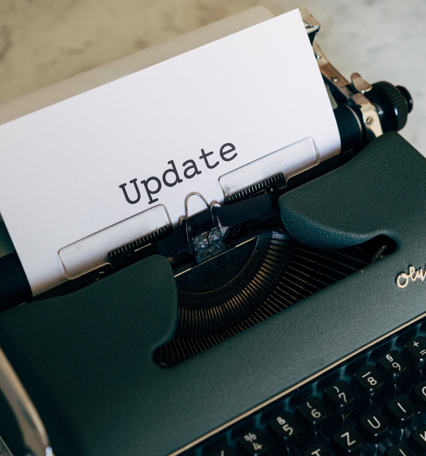 "A typewriter with a piece of paper that read ""UPDATE"". Image by Pexels: Marcus Winkler"