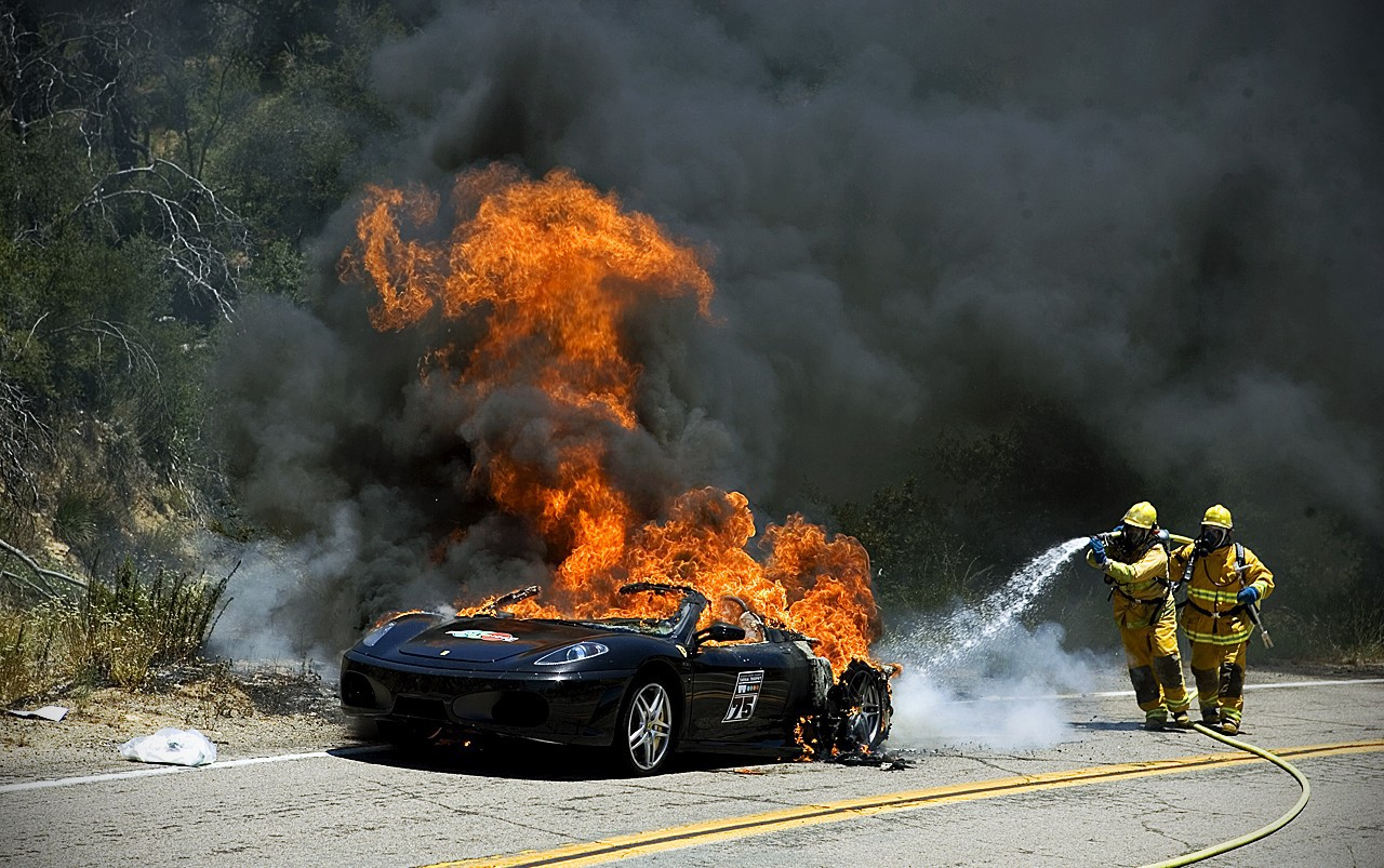 Firefighters trying to douse a burning electric vehicle