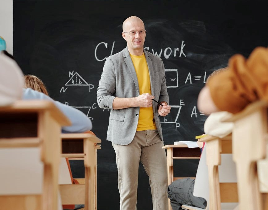 Students sat at their desks looking at a teacher standing in front of a blackbord