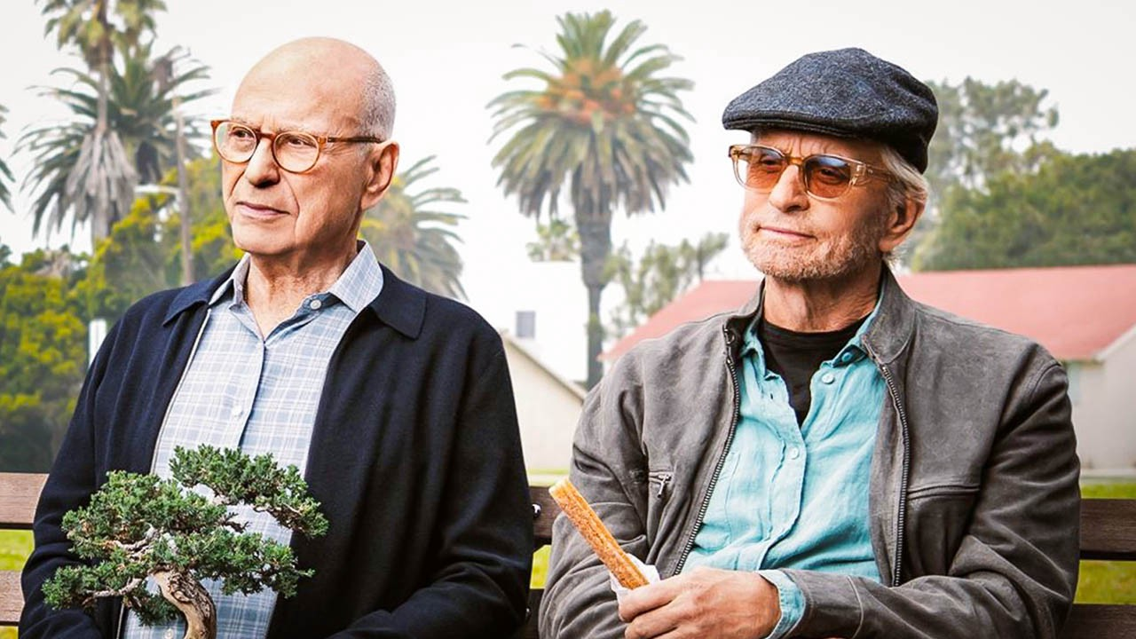 Alan Arkin in shirt and cardigan, left, seated on a bench holding a bonsai tree with Michael Douglas in wool cap and sunglasses.