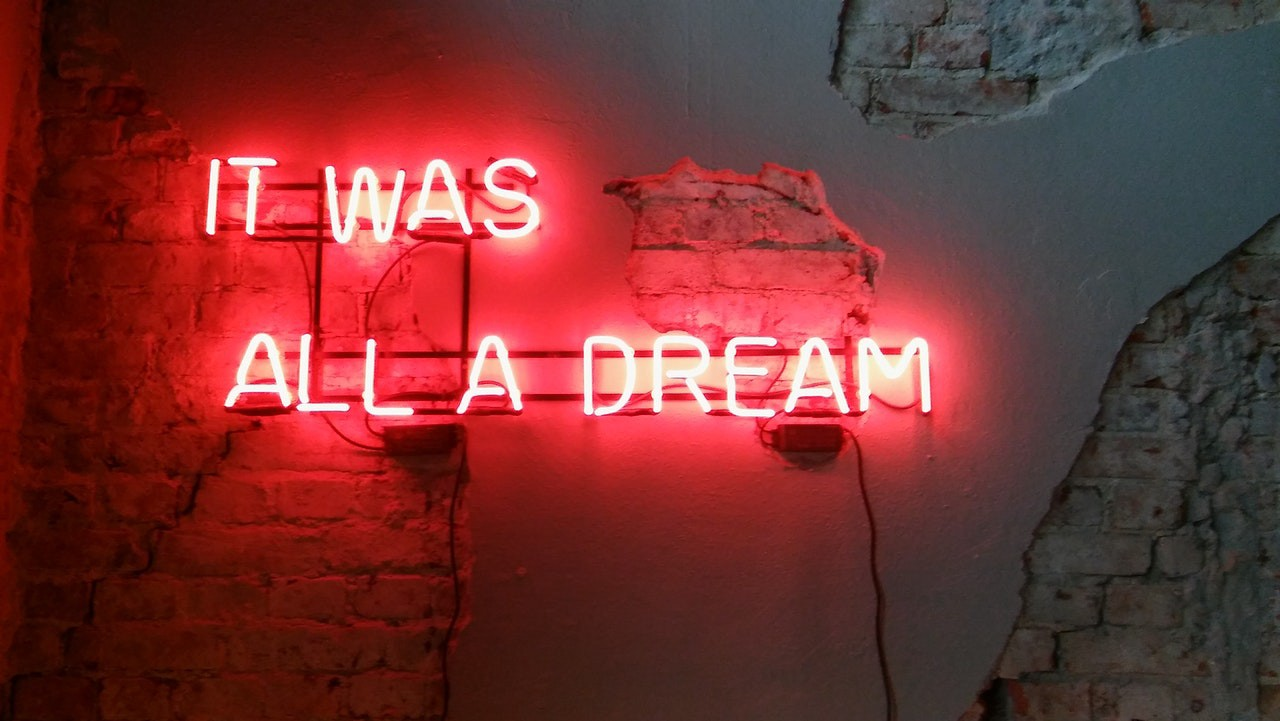 """Neon sign on a brick wall says, """"It was all a dream"""""""