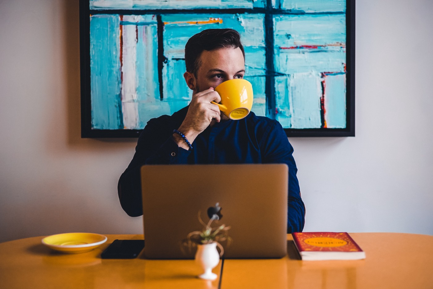 Man sips from a yellow mug while using a laptop. Angular oil painting on the wall behind him.