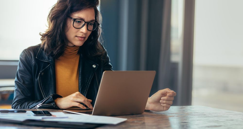 Asian woman working laptop at contemporary office in casual attire