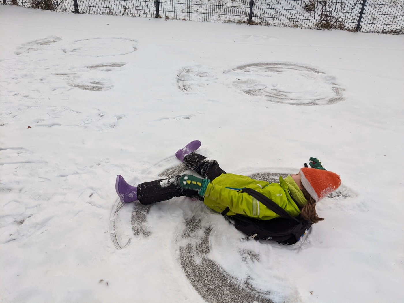 A child making a snow angel on a concrete basketball court.