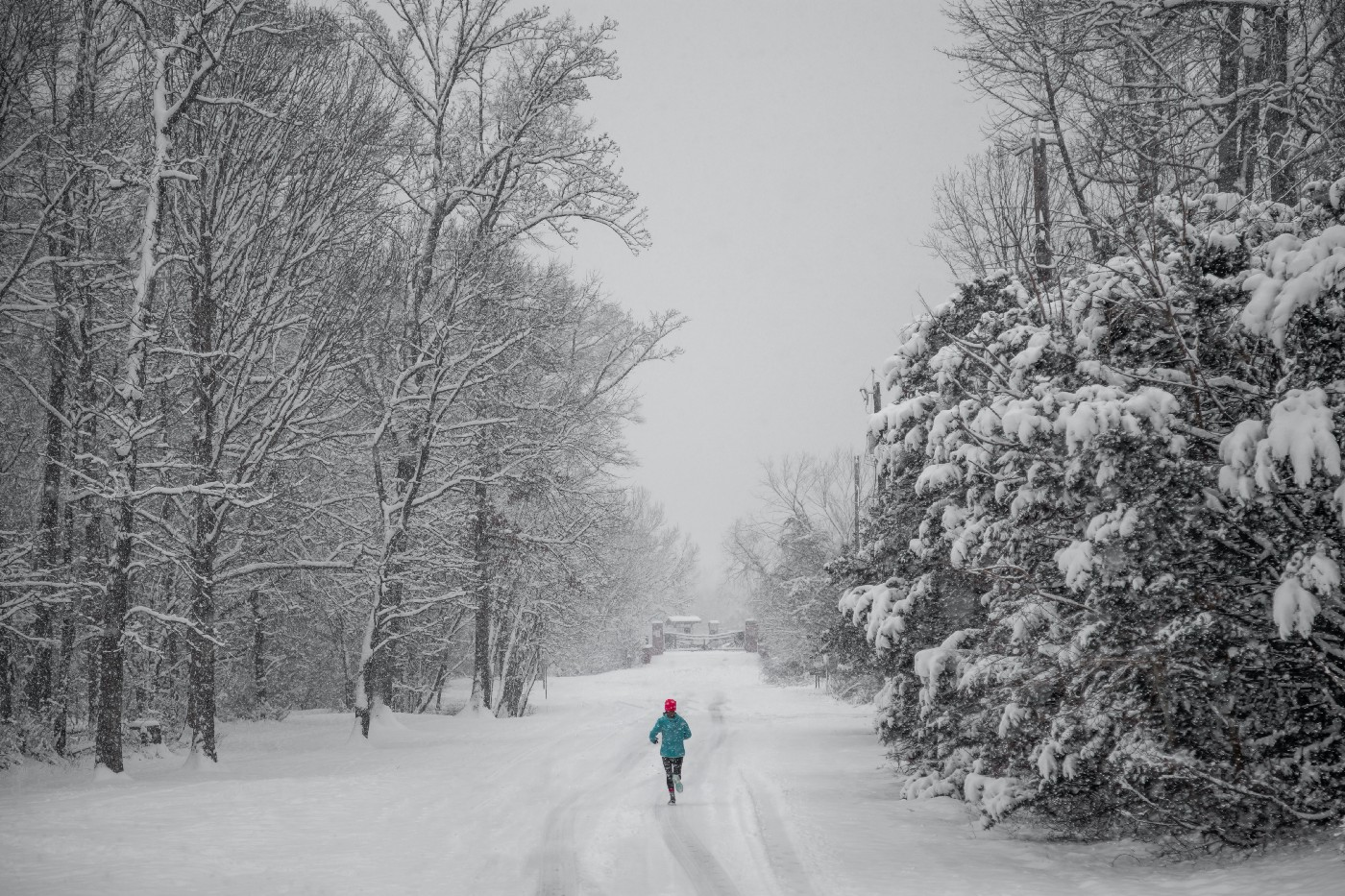 A person is running on a snow covered road in the woods.
