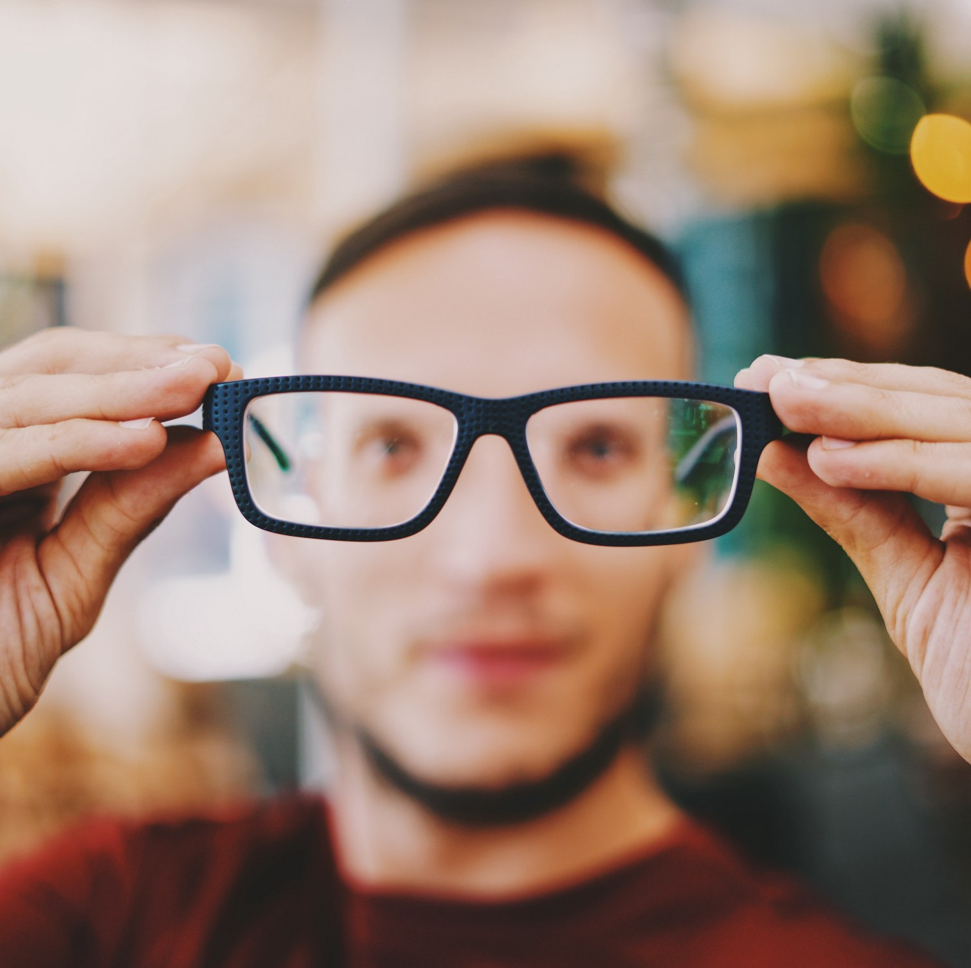 Man holding his glasses away from his face bringing the world into focus