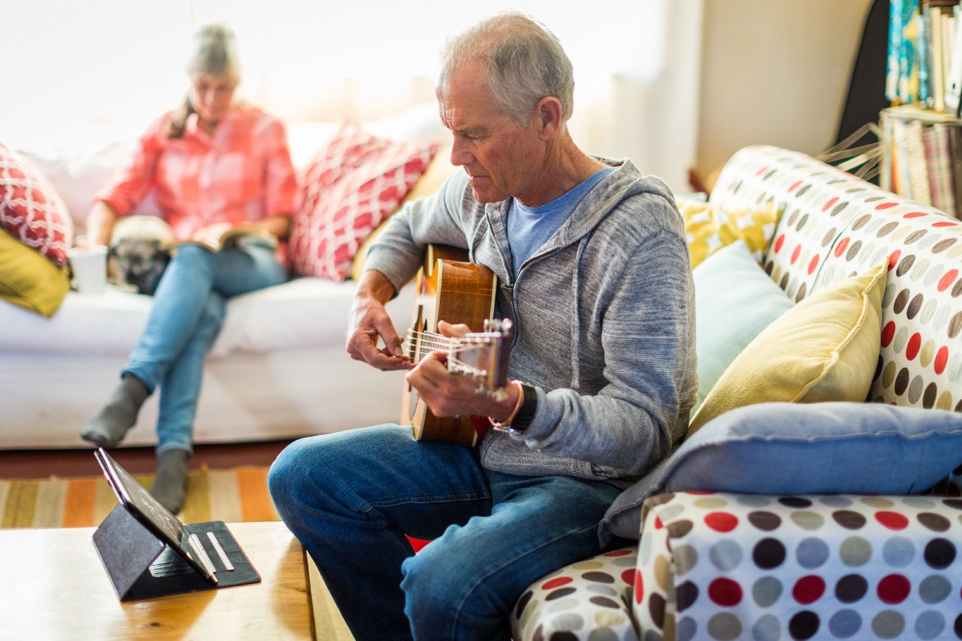 An older man learning guitar by watching an online tutorial on his tablet.