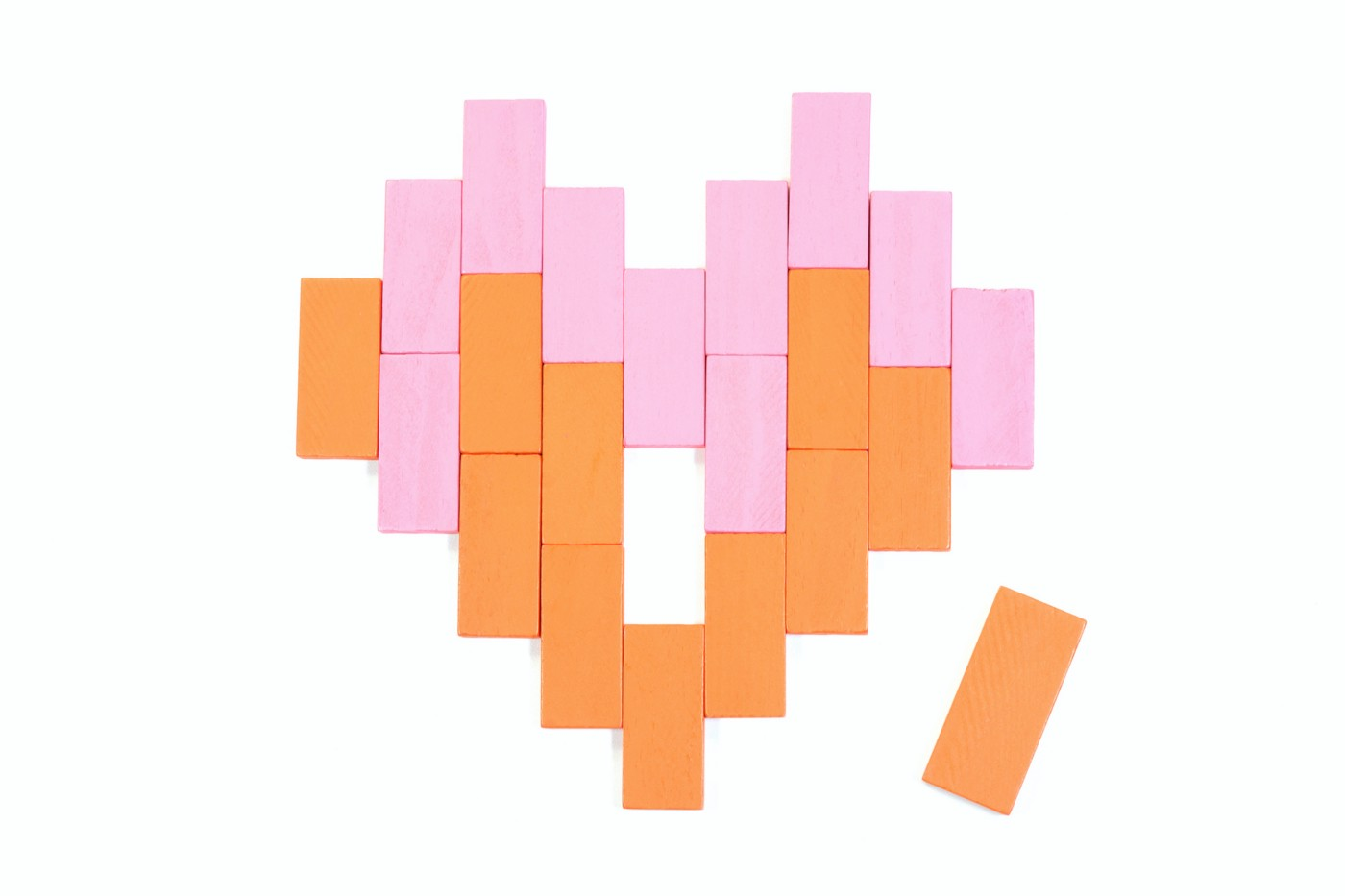 Orange and pink rectangular blocks arranged in the shape of a heart with one piece missing (an orange one next to the heart)