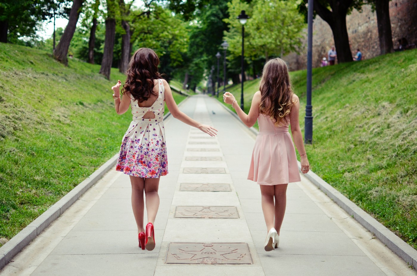 Two teenage girls in dresses walking away from the camera on a sidewalk with green hills on either side of it.