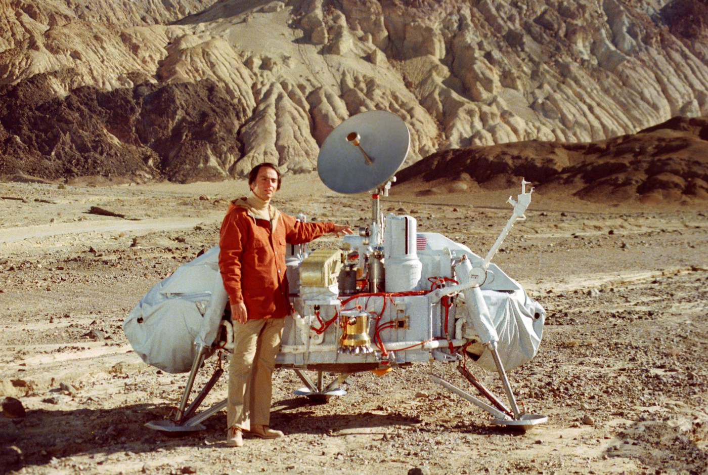 Carl Sagan stands beside a lunar lander craft in an orange jacket and beige slacks.