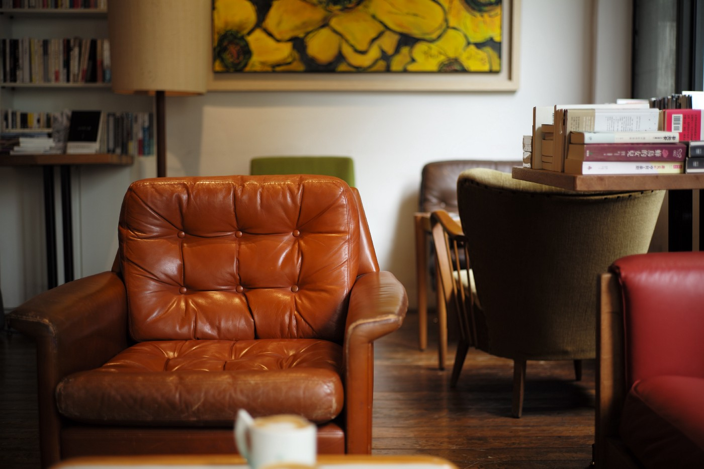 A brown leather club chair is the focus with a desk and other chairs in the background.