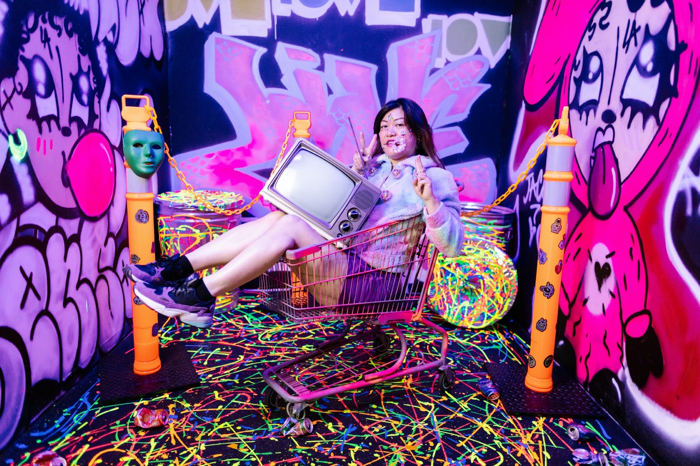 Fun and chaotic messy photograph of woman in shopping cart with an old television in her lap. Graffiti, green mask, colorful floor. General tomfoolery.