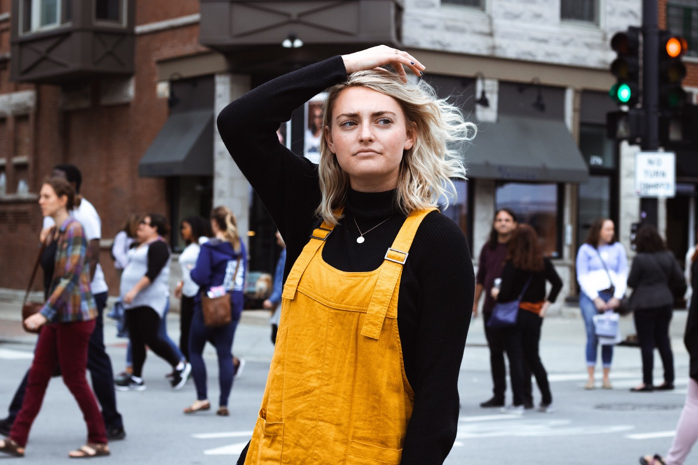 A young woman in a black turtleneck and gold overalls stands alone, lost in her thoughts, at a busy urban intersection.
