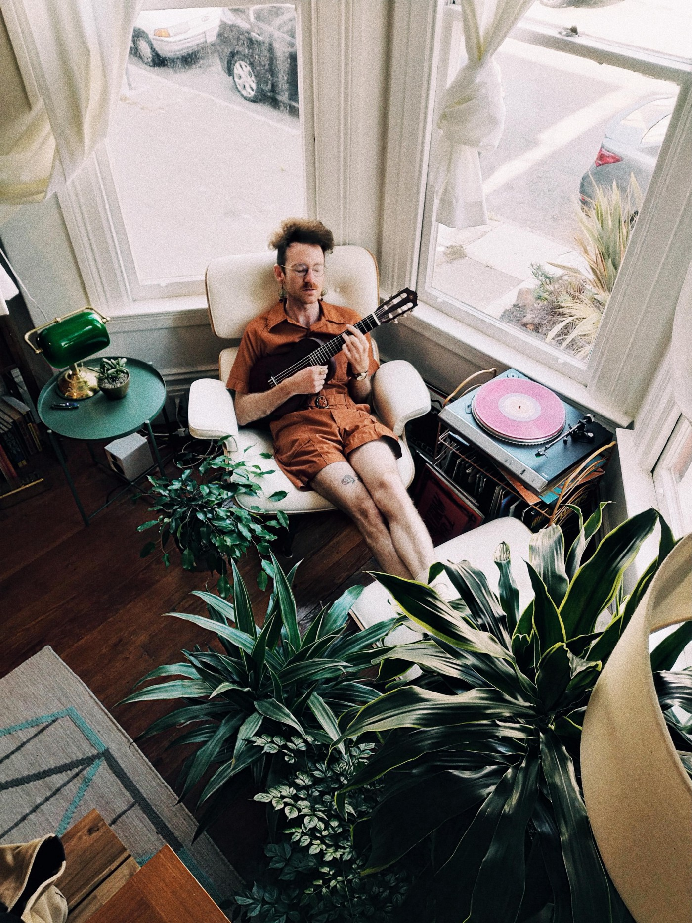 A young man chilling in an armchair, playing his ukulele next to a vintage record player.