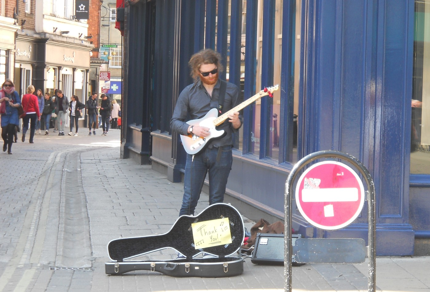 Man busking on a street corner in York, playing a Fender Telecaster electric guitar with his guitar case open at his feet to collect any coins donated to him by members of the public
