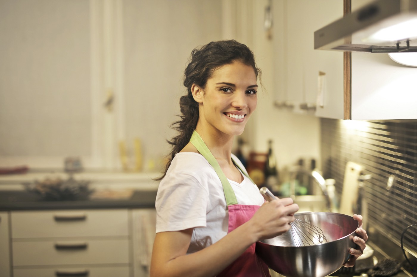 Woman in the kitchen holding a bowl and a whisk