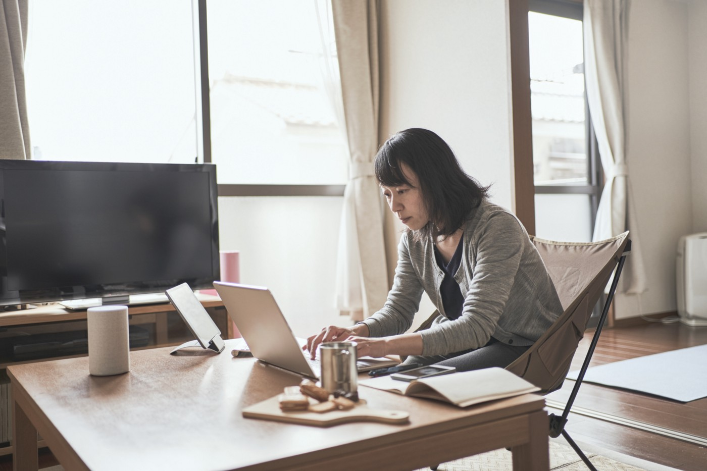 Asian woman working on her laptop in her living room.