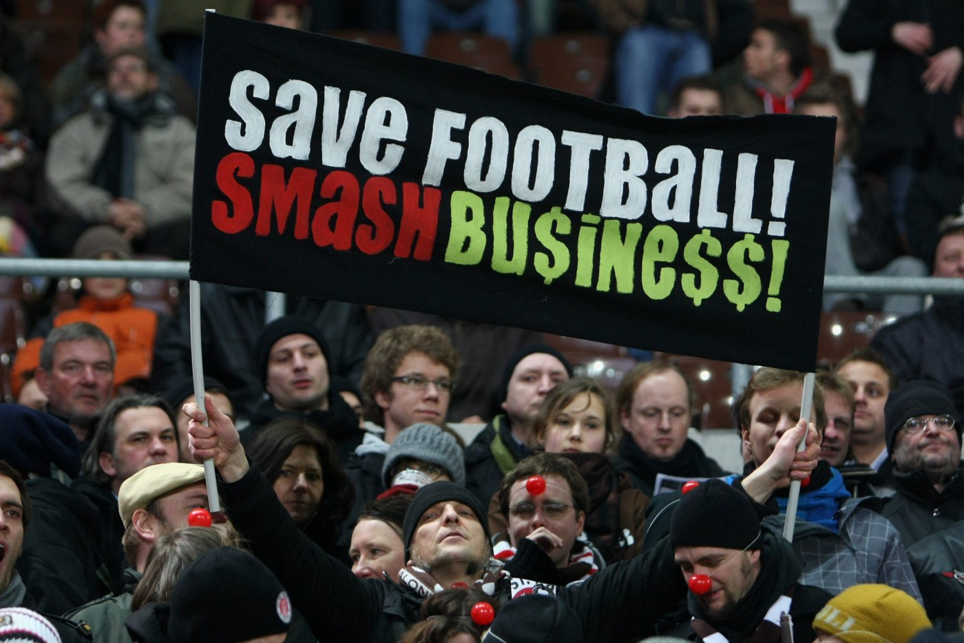 """Fans of German football team St Pauli show their dismay at the influence of big business on football prior to a match against FC Kaiserslautern in Hamburg with a banner saying: """"Save football! Smash Business!"""""""