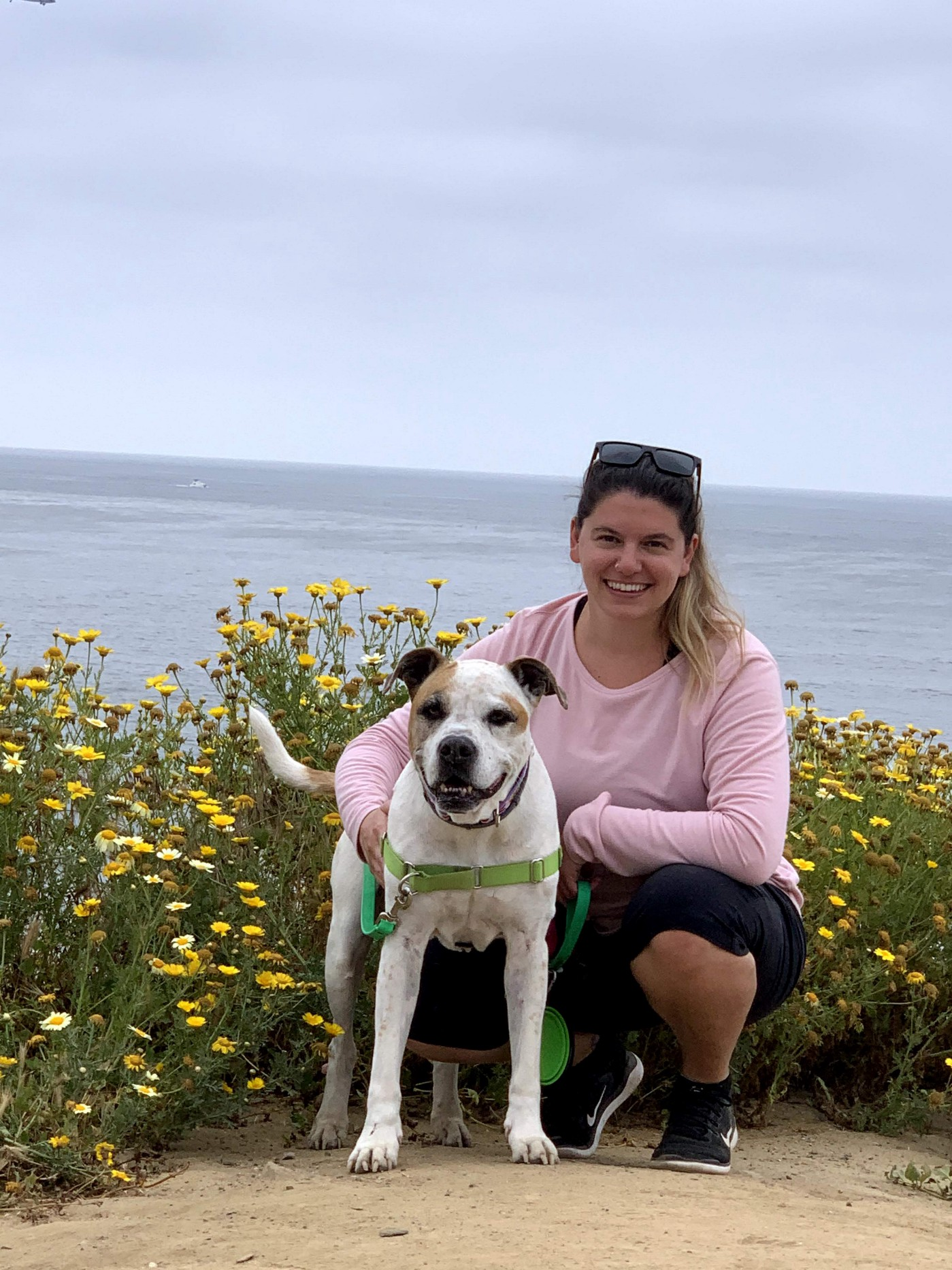 Sandra with her dog that looks like a pitbull mix in front of an ocean and yellow flowers