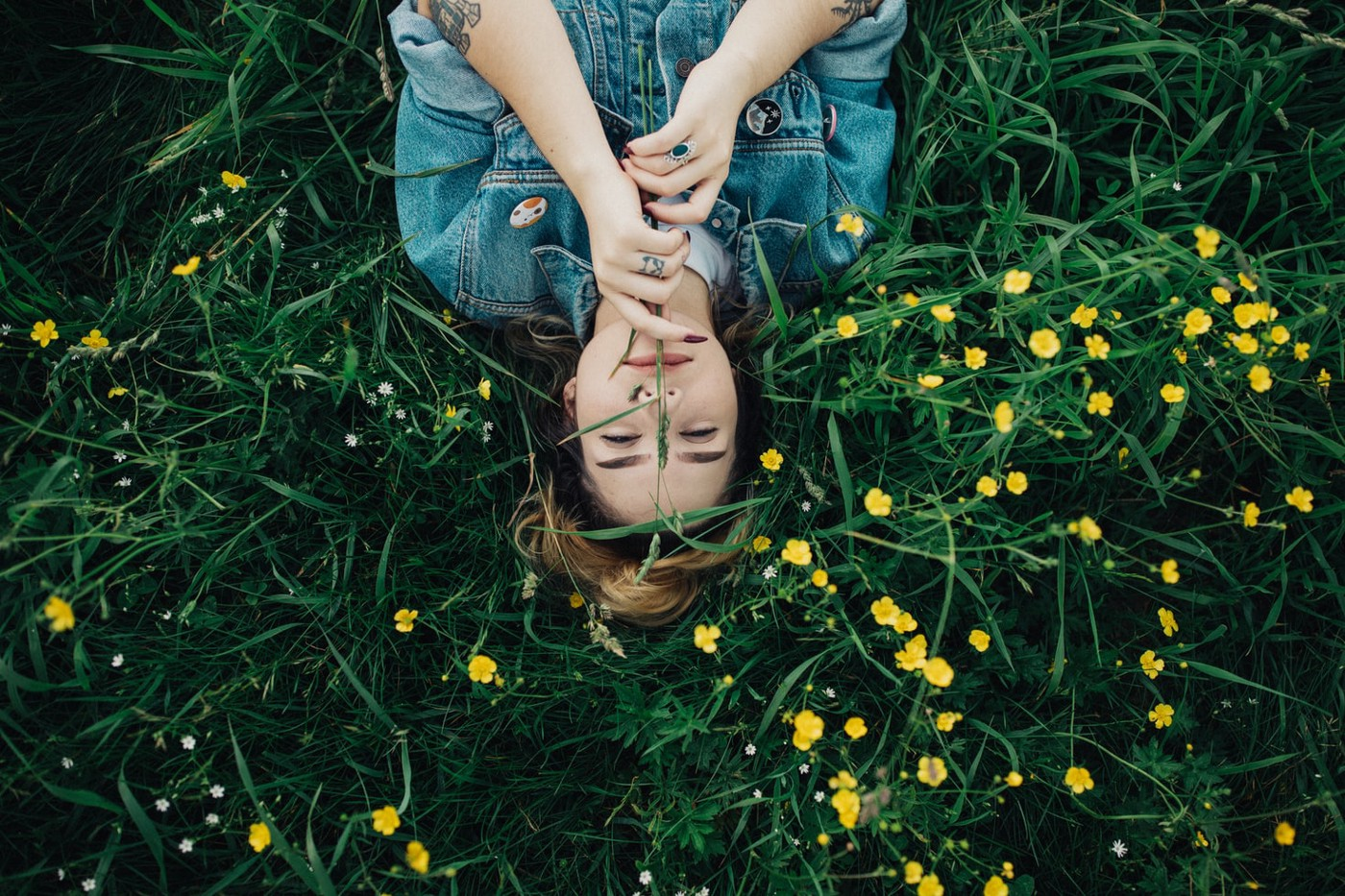 A young woman lays in the grass with a smile on her face. Yellow flowers surround her.
