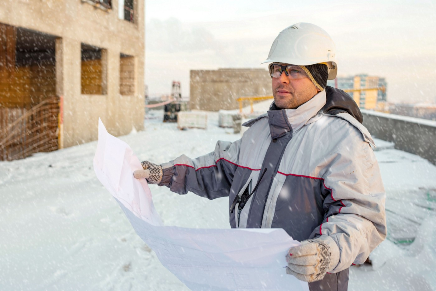 A civil engineer is holding up blueprints while in snowy weather, determining how they'd want to use their concrete admixtures.