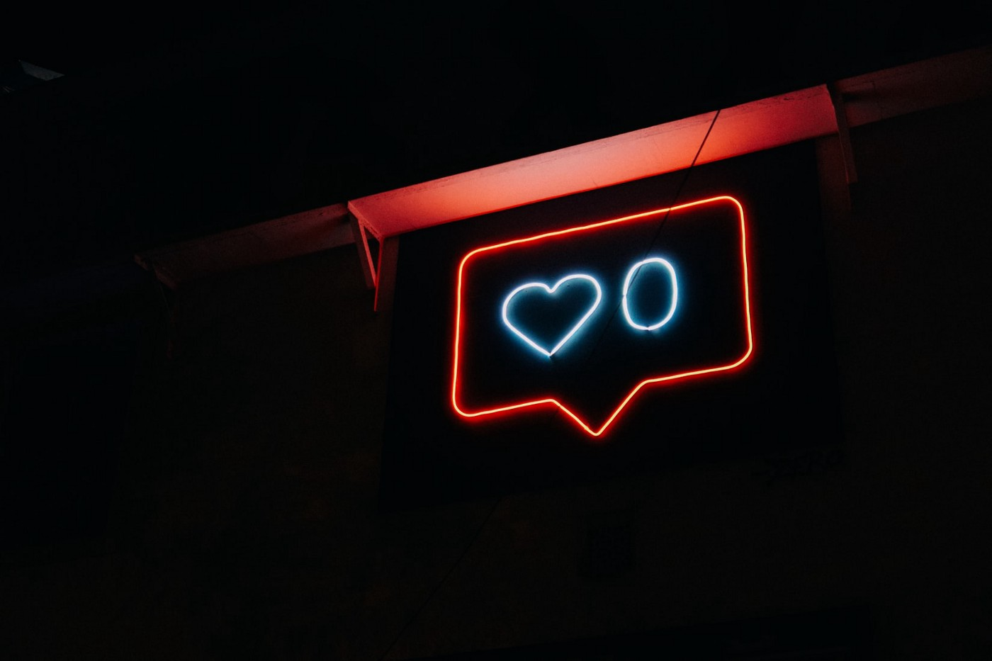 Neon signage of a social media heart icon with a zero next to it.