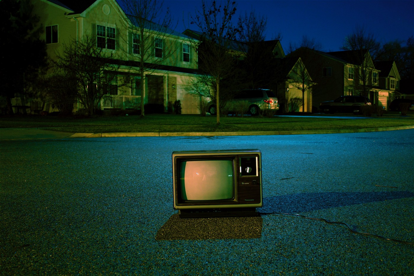 An old box-style TV on the ground in the middle of a suburban street