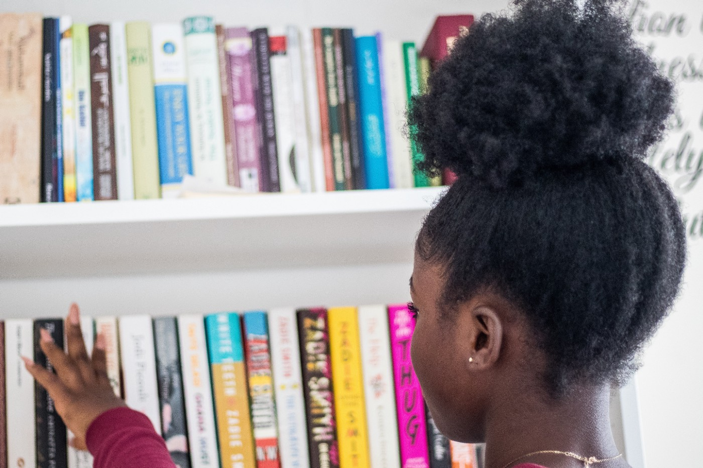 a young Black girl runs her fingers over the spines of books stacked on a white bookshelf