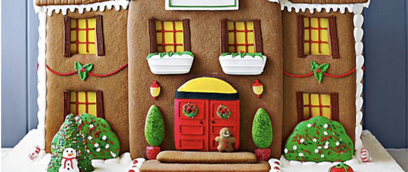 A very fancy gingerbread house with a red door.