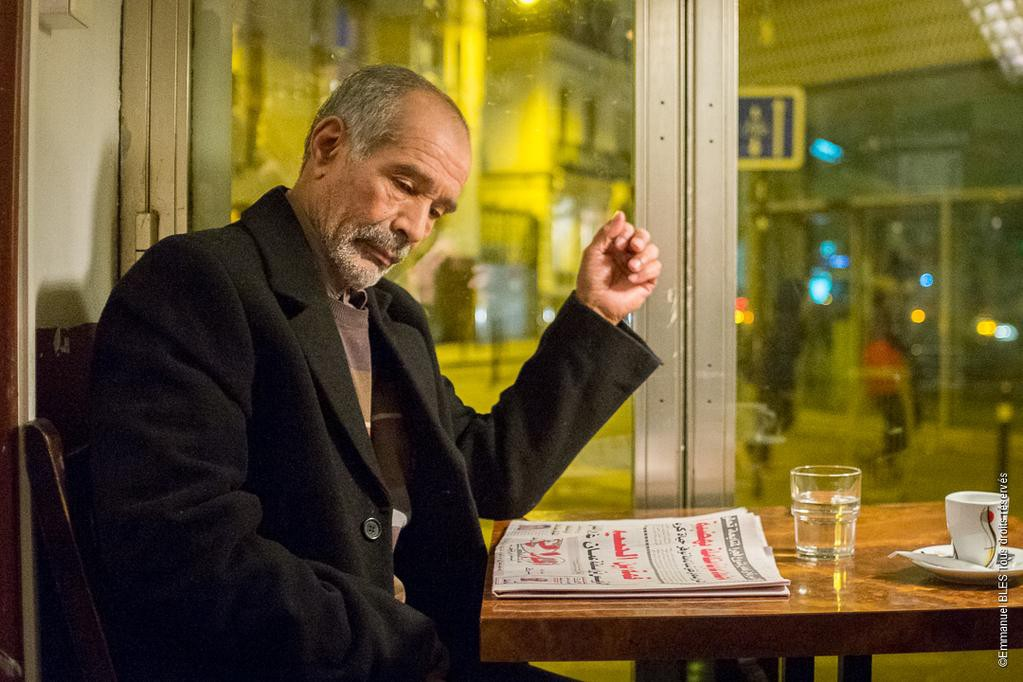 An older man sits in a cafe reading a newspaper.