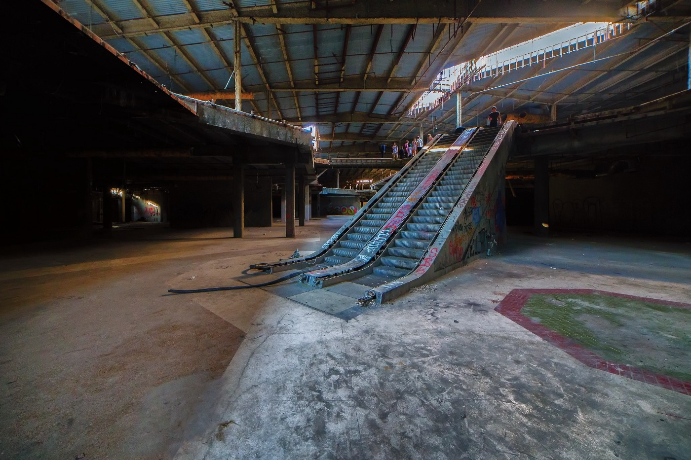 Interior of a dilapidated abandoned mall with escalator and floor tiles prominently featured