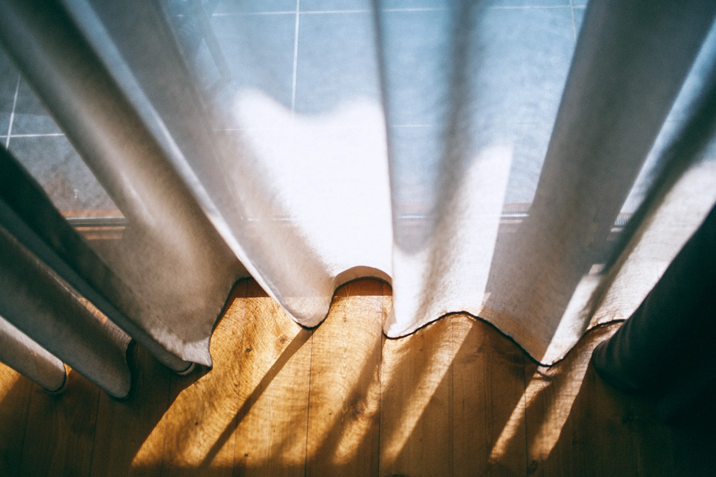 Sunlight streams through curtains behind a window.