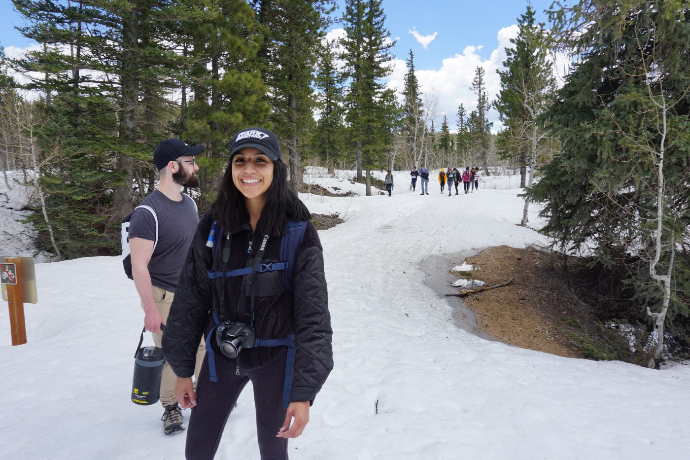 Lory heads a hike on a snowy trail featuring a group of people behind her and a guy next to her