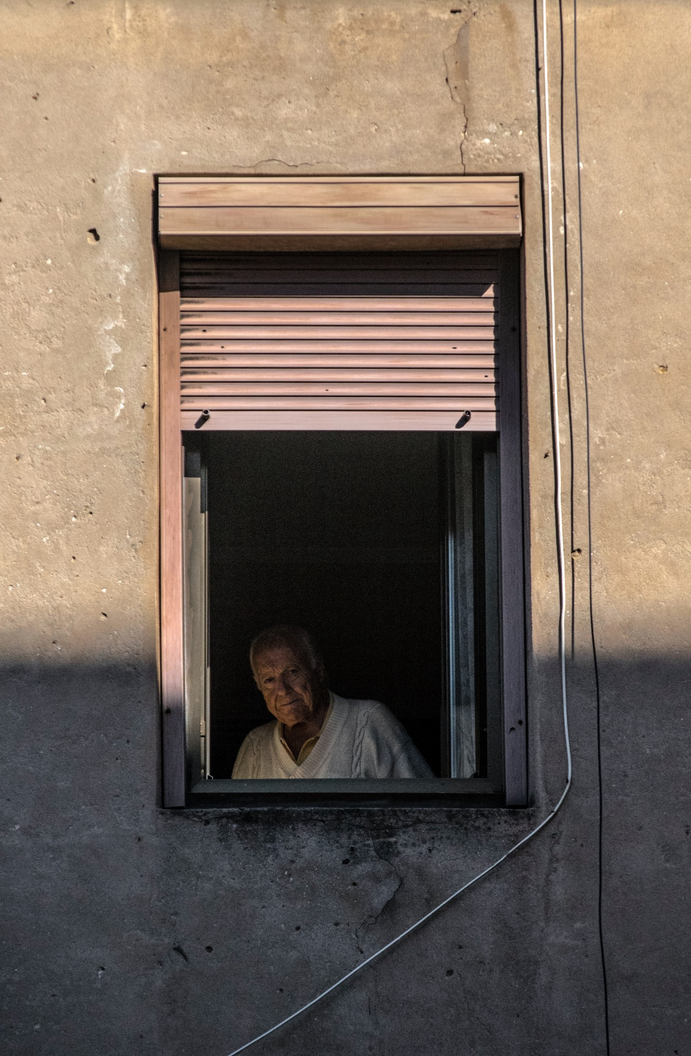old man sitting in darkness, wearing a white shirt, looking out of his window.