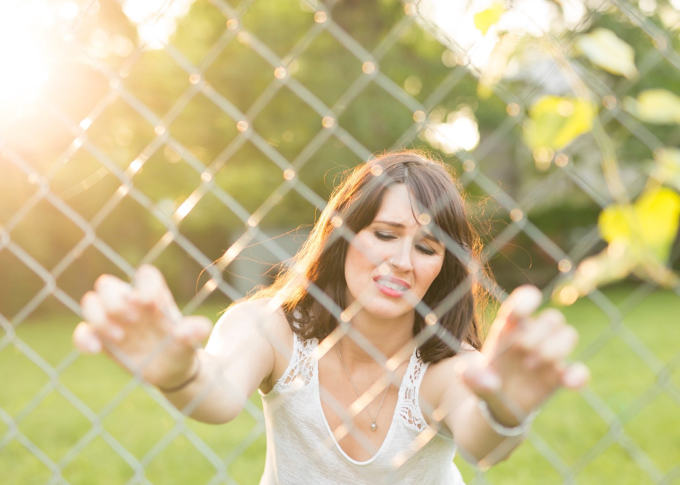 Woman looking frustrated holding on to a chain link fence.