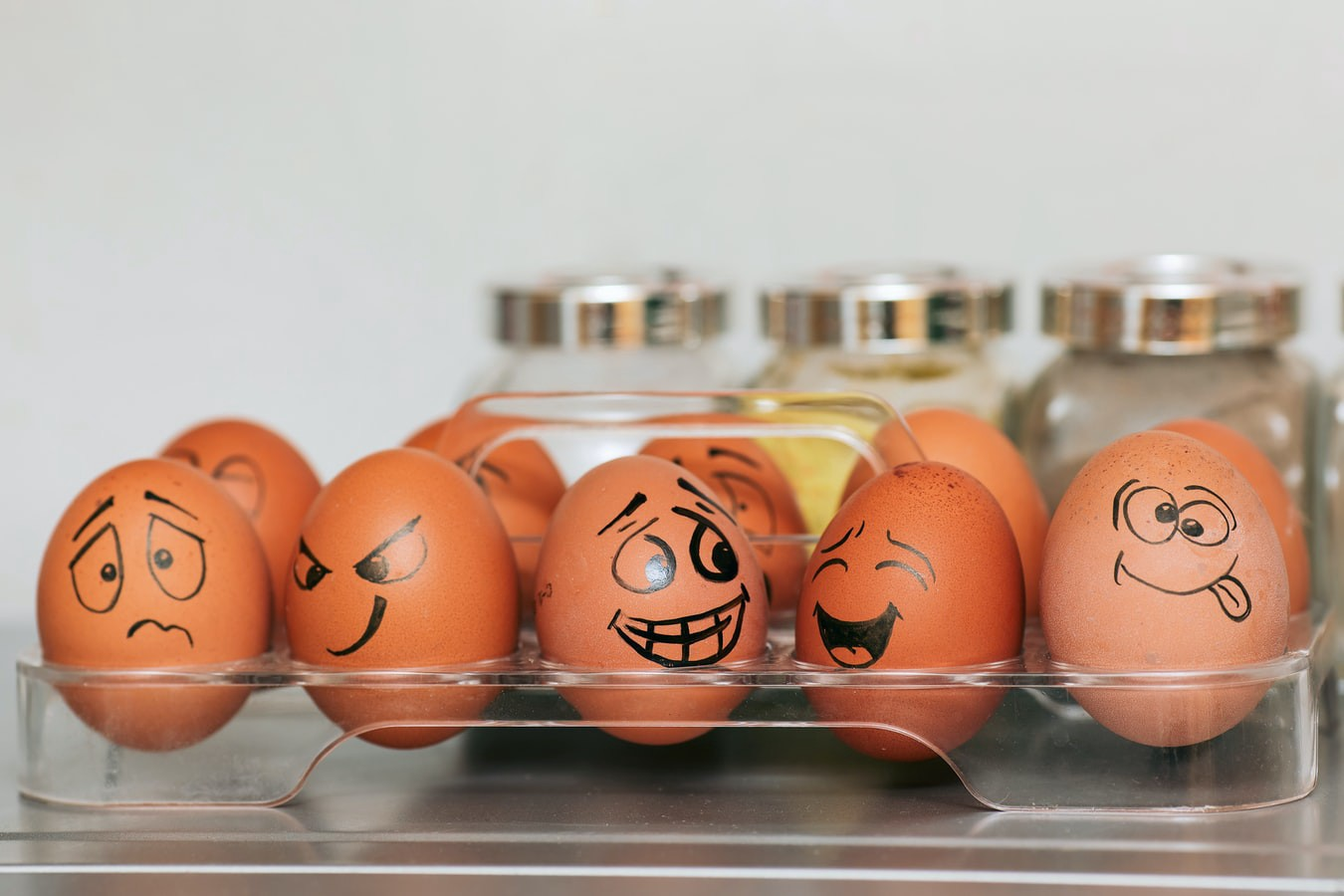Eggs with faces of different emotions drawn on them, sitting in a transparent holder.