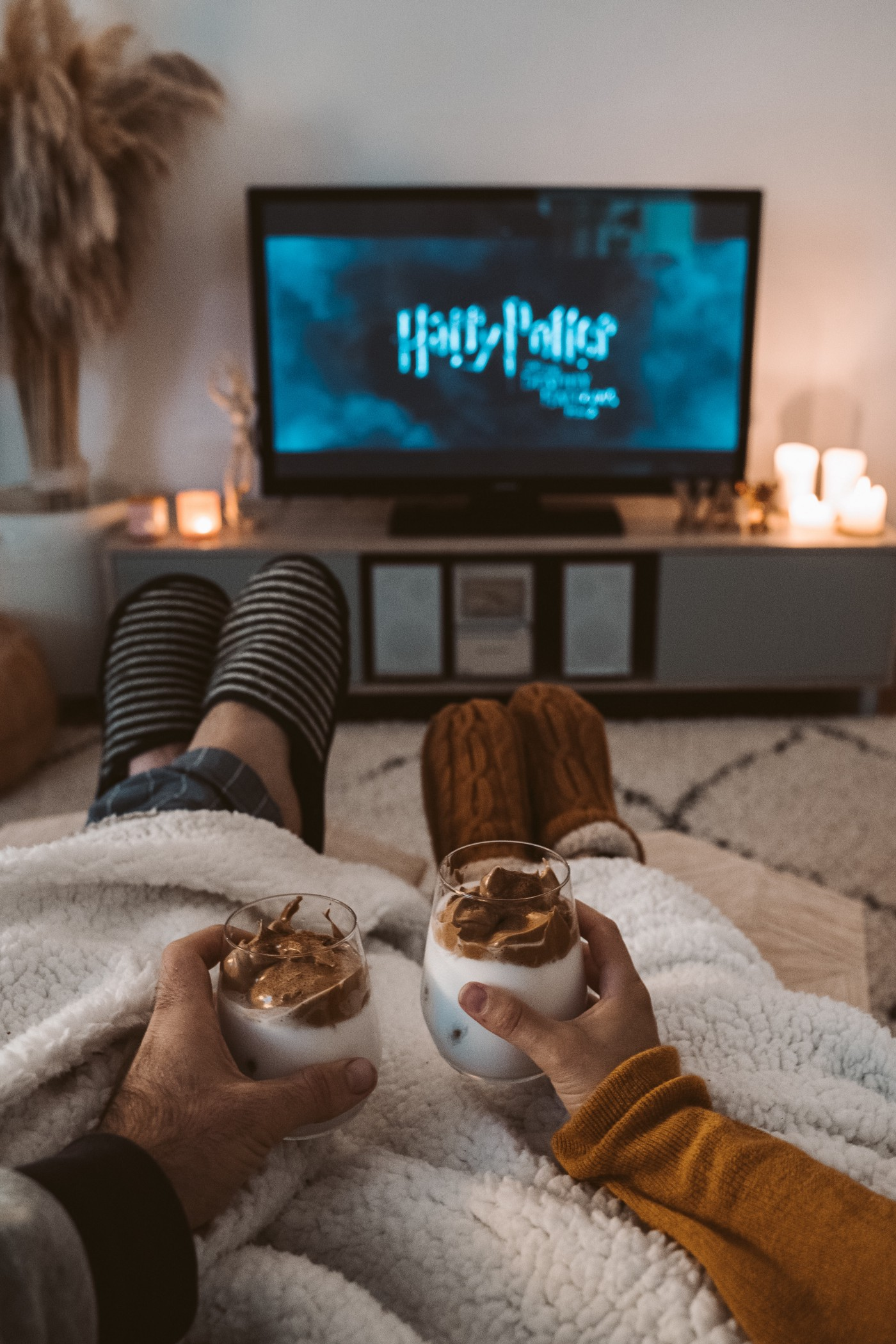 A couple watching TV with slippers on drinking coffee
