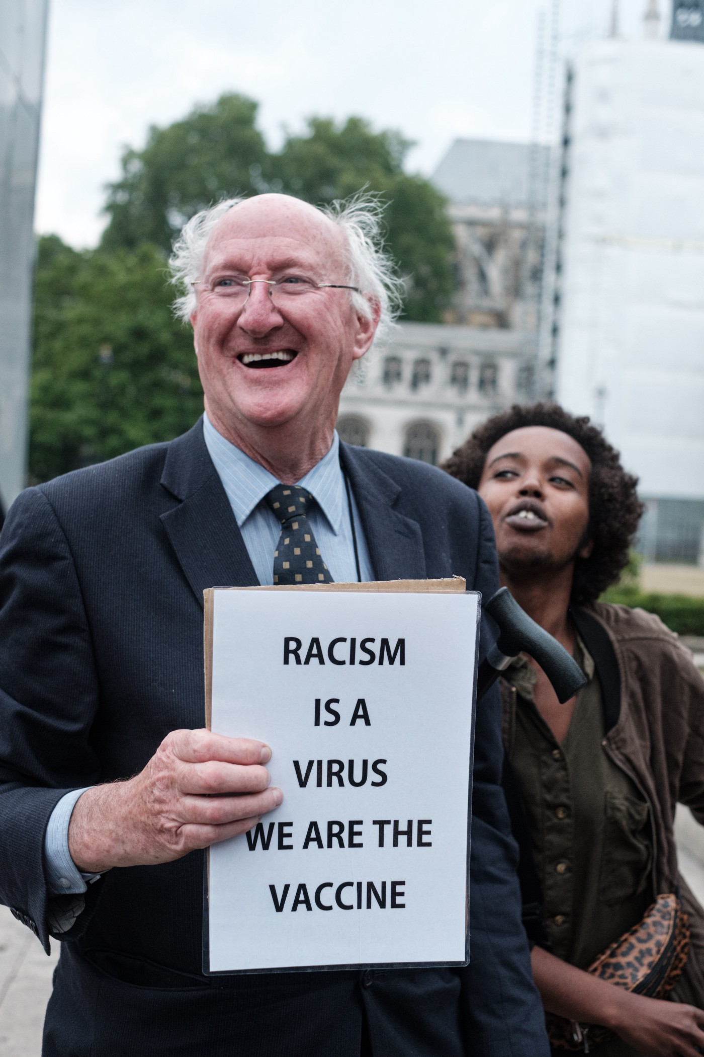 """White man holding a sign smiling and a black woman standing beside him. The sign reads """"Racism is a virus, we are the vaccine."""""""