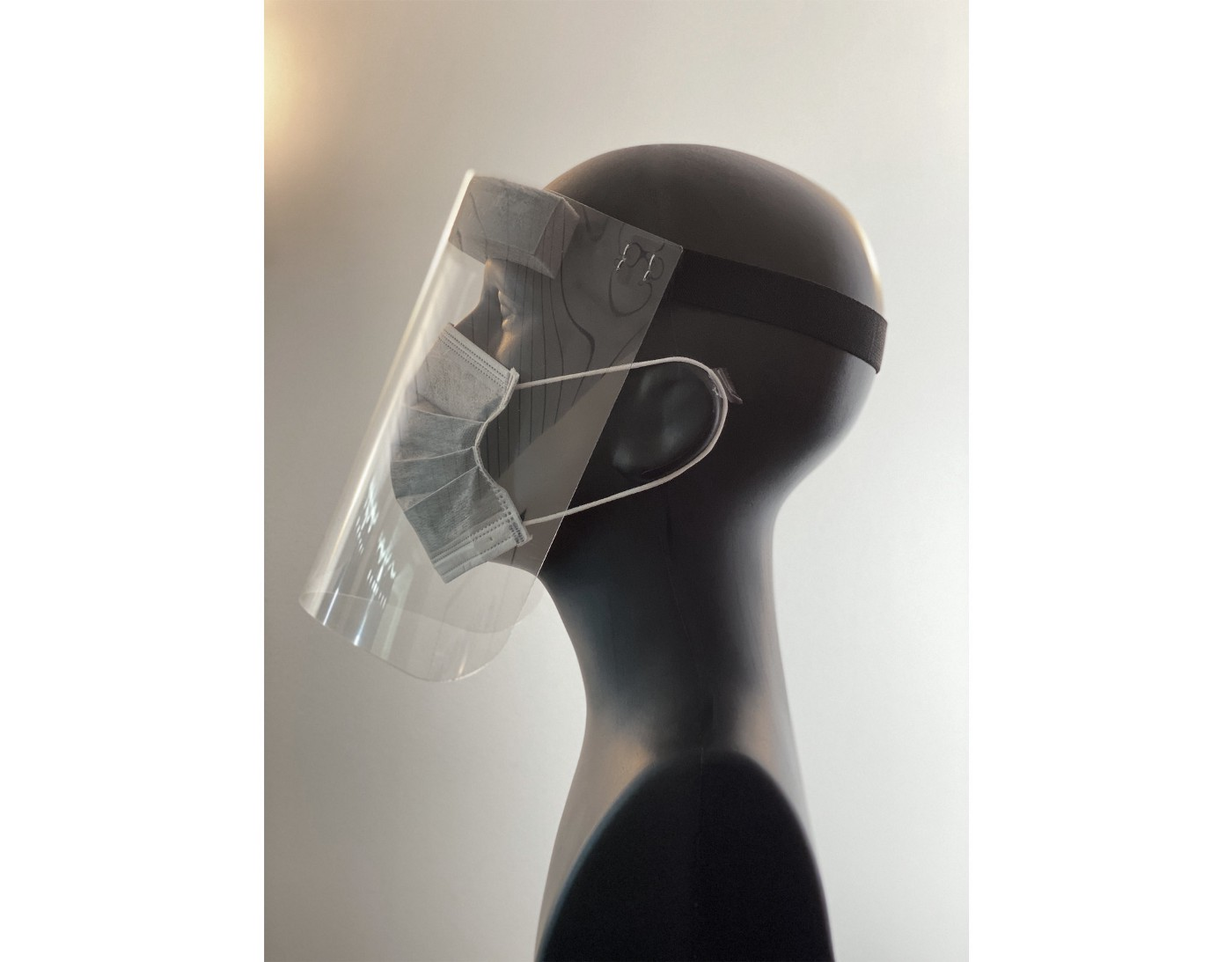 A mannequin wears a medical mask and face shield