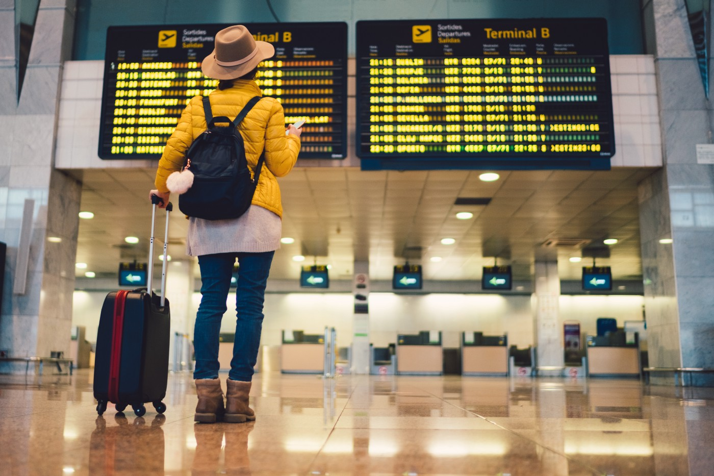 A traveler with a backpack and a rolling suitcase looks at arrivals boards at the airport.