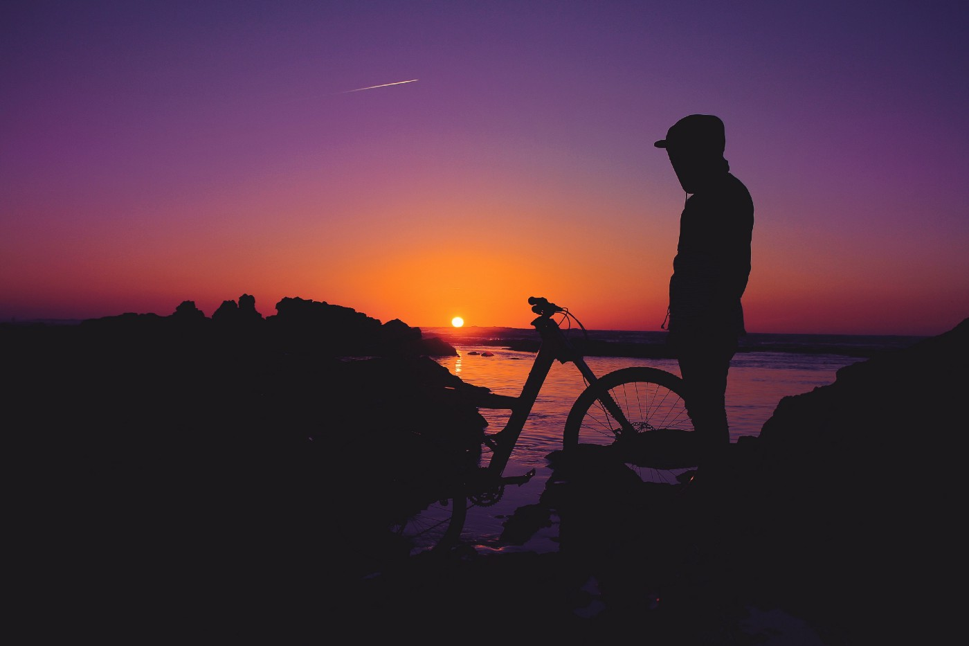 The silhouette of a man standing by his bike at sunset.