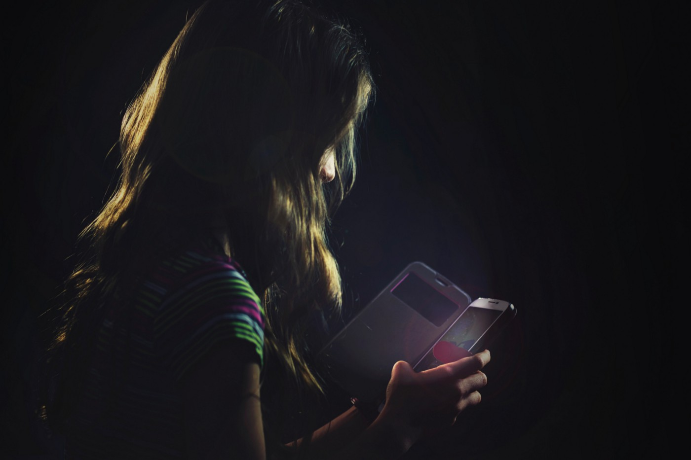 Dark photo of a young girl on a smartphone.
