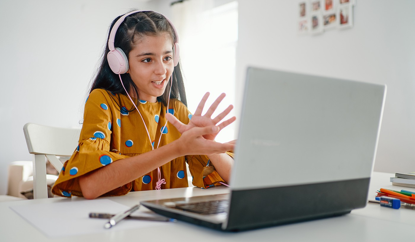 A middle school student in a yellow dress with blue polka-dots uses headphones while working at a laptop.