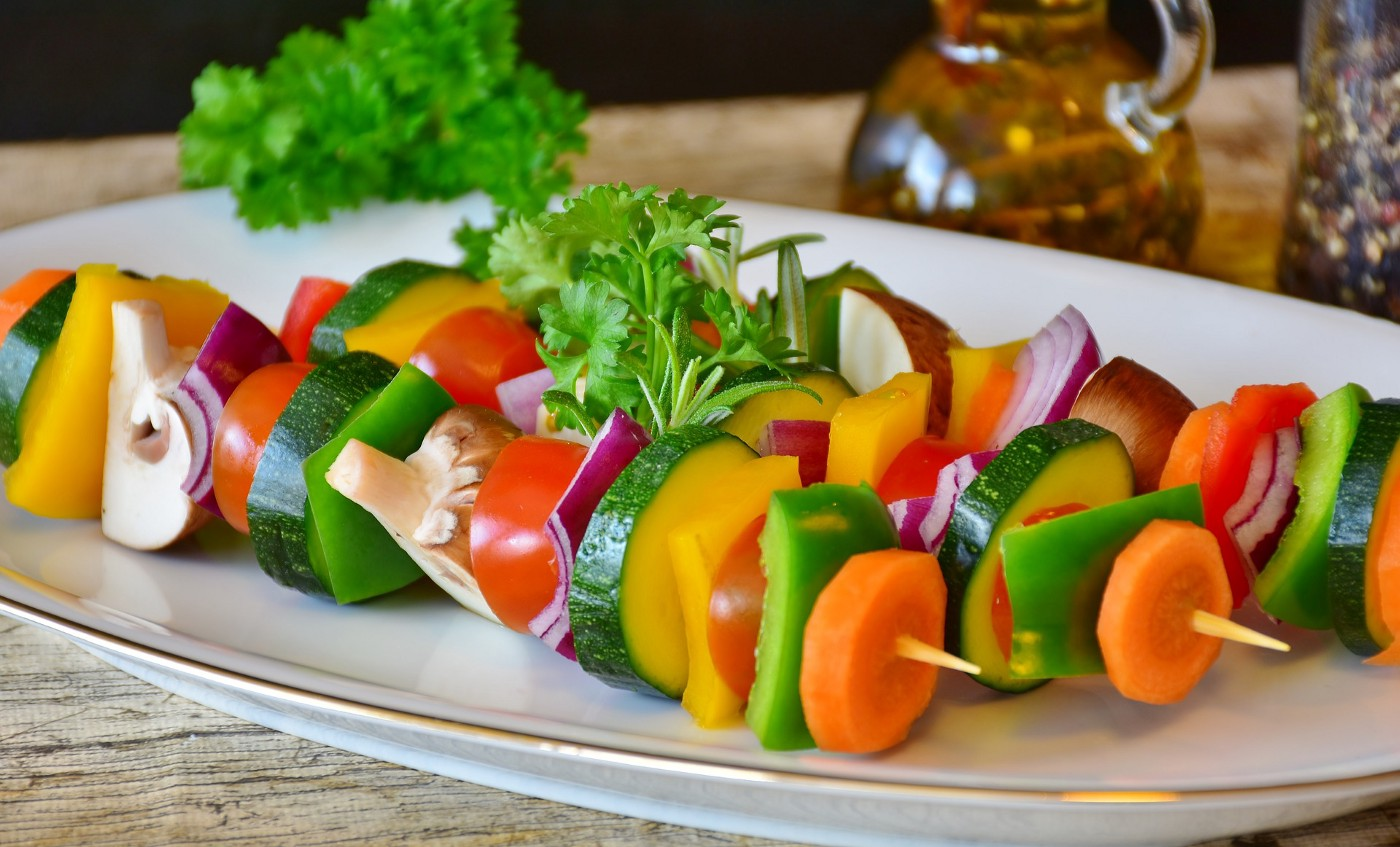 Three raw vegetable skewers with carrots, onions, mushrooms, zucchini, peppers, and tomatoes